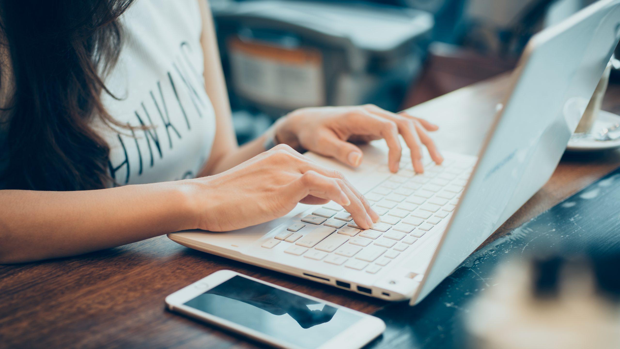 Mulher digitando no notebook; há vagas para profissionais da tecnologia