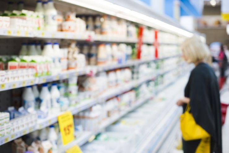 Mulher no supermercado vendo laticínios, que são produzidos graças à Zootecnia