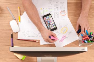 Marketing digital - Na foto, vemos de cima mãos fazendo anotações em papeis, com um celular cheio de aplicativos no meio, e em frente a um computador.
