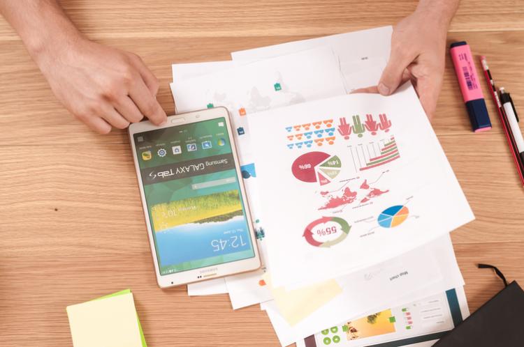 Renda extra para MEIs - na foto, há diversos objetos em uma mesa relacionados às vendas online, como um tablet e gráficos coloridos com porcentagens que mostram diversos perfis de consumidor