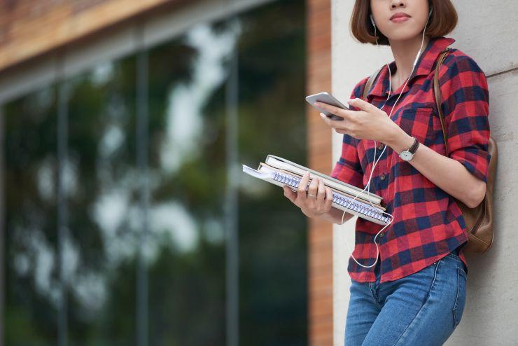 Mulher encostada em parede com livros e celular nas mãos; Bolsa Superamos Juntos busca apoiar manutenção de estudos de universitários