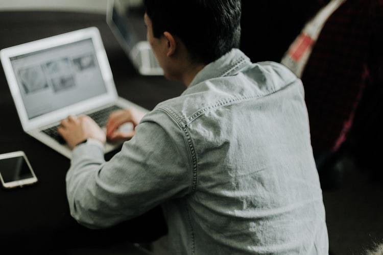 Cursos online: na foto, vemos um homem de costa, de frente para um notebook