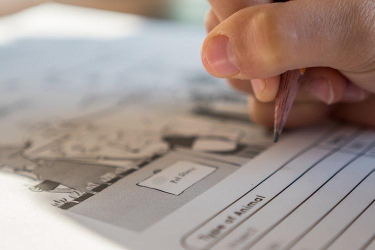 Mão preenchendo prova; cursos online estão com inscrições abertas