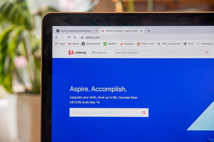Na imagem, vemos metade de um notebook. Na tela, há um navegador aberto com a página da plataforma Udemy, com uma barra de busca e fundo azul. Design gráfico é área com cursos ofertados pela Udemy