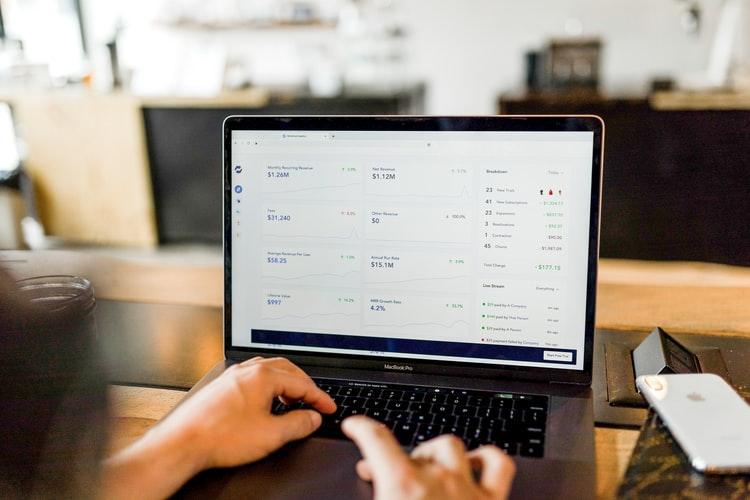 E-commerce - Na foto, vemos duas mãos digitando em um notebook. A tela mostra gráficos e análise númericas e verbais, que parecem mostrar ferramentas de marketing digital. O fundo está desfocado.