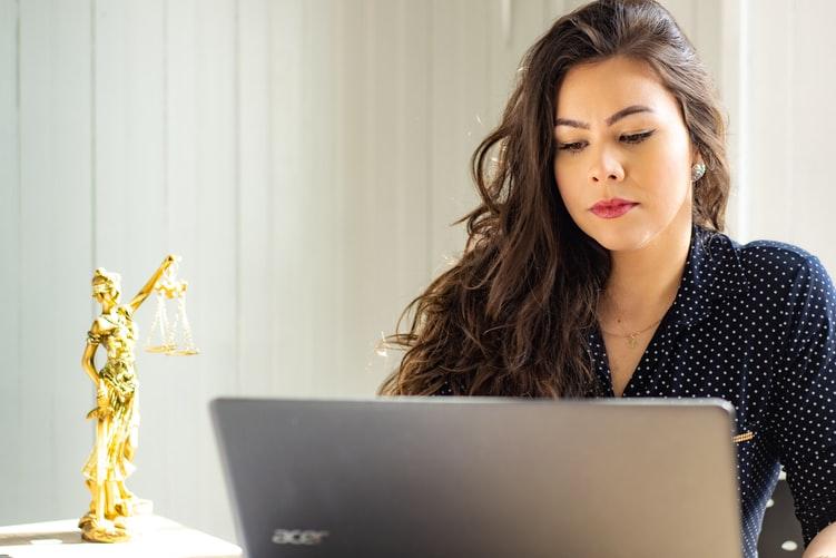OAB - Na foto, uma mulher está olhando para a tela do Notebook, como se estivesse estudando. Ao lado, há uma estátua da justiça, símbolo do curso de Direito.