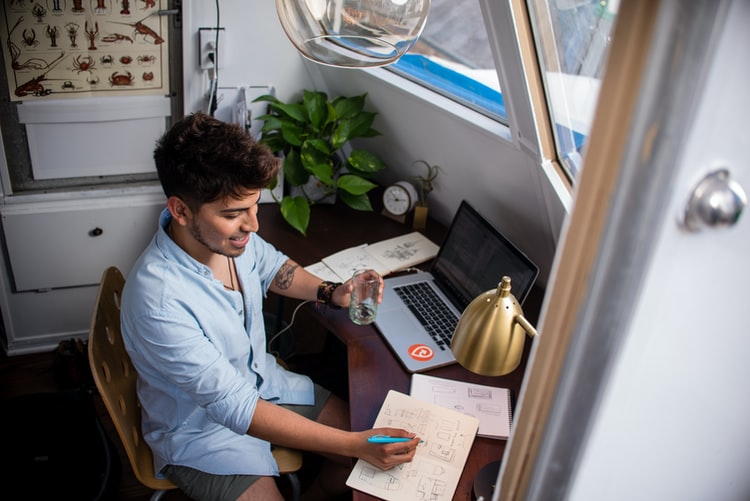 Na imagem, um homem de camisa social está sentado em frente a um computador, fazendo anotações em um bloco de notas e sorrindo. Há plantas e um relógio na mesa, além de um notebook e papeis; Senac Ceará oferta oportunidades
