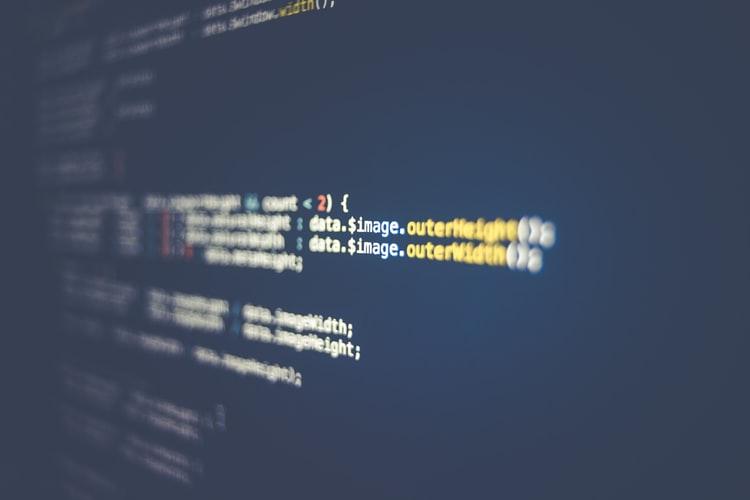 Santander - Foto mostra a tela de um computador com fundo azul e diversos códigos de programação nas cores branca, amarela e vermelha