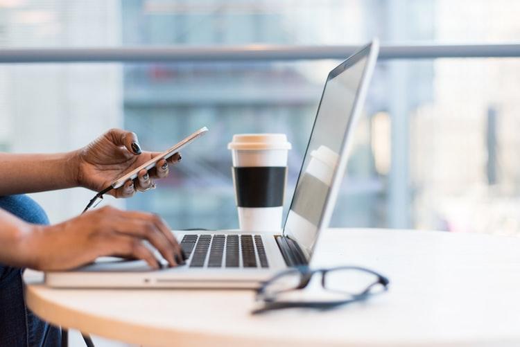 Na foto, vemos duas mãos em frente a um computador; a esquerda segura um celular e a direita digita em um notebook. Atrás do notebook há um copo branco, em um modelo tipicamente usado para café. Na frente do notebook, desfocado, há um óculos de grau. As mãos são femininas, negras e as unhas estão esmaltadas com a cor preta. O notebook, o copo e os óculos estão em cima de uma mesa de cor clara, que está desfocada na imagem.