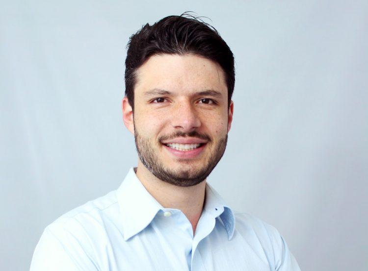 Na foto, o empresário Jeison Schneider, CEO do Meu Crediário, sorri para a câmera. Ele usa uma camisa azul clara de botões, e possui cabelo e barba pretos e curtos.