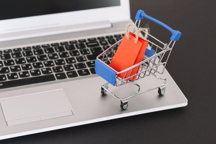 Carrinho de compras em miniatura em cima de notebook, fazendo referência a vendas online