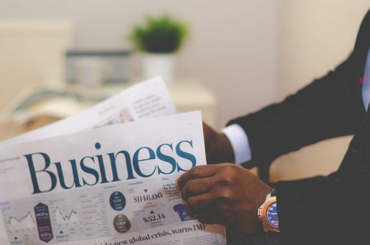 """A imagem mostra um par de mãos de um homem negro abrindo uma revista cujo título é """"Business"""". No punho direito do homem, há um relógio dourado. Ele usa terno preto e camisa social branca. No fundo da imagem, há uma planta em cima de uma cômoda."""