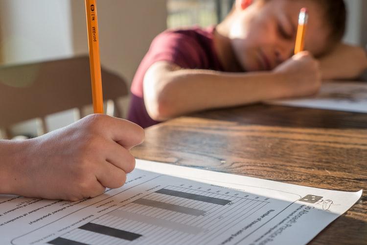 Na foto, há uma mão masculina escrevendo com um lápis amarelo em um papel com gráficos. Em segundo plano, há uma criança de aproximadamente 6/7 anos escrevendo em um outro papel com um lápis similar.