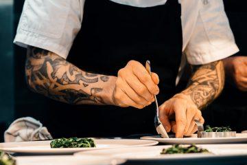 A foto mostra um chef preparando a apresentação de pratos. Os dois braços do homem, que é branco, são tatuados. O rosto não está visível, apenas uma camisa branca e um avental preto.