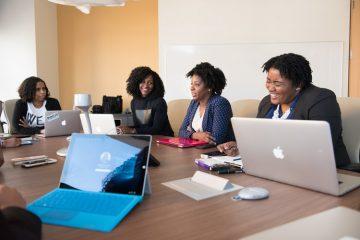 Na imagem, um grupo de mulheres se reúne ao redor de uma mesa marrom e grande de reunião. As três tem cabelo crespo, usam terninhos e sorriem enquanto parecem conversar. Na mesa, há diversos computadores, mouses e cadernos.