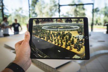 Realidade aumentada: a foto mostra um tablet que reproduz imagem de realidade aumentada de um parque com muitas árvores. No fundo, há janelas de vidro e o dia está claro. Uma mão masculina segura o tablet do lado esquerdo.