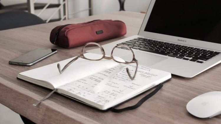 Na imagem, há uma mesa de madeira com alguns objetos em cima: um estojo vinho, à esquerda; um notebook cinza aberto com a tela preta, ao lado do estojo; e à frente do estojo, um caderno aberto com anotações e um óculos de grau de cor marrom