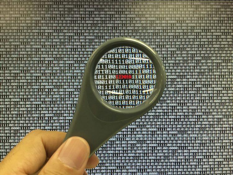 Vagas de trabalho no ramo da tecnologia: Na imagem, uma mão segura uma lupa em frente a uma tela com vários códigos de programação
