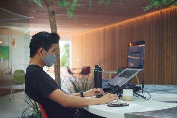 CESAR oferta possibilidade de trabalho remoto e flexível. Na imagem, um homem de camisa preta e máscara cinza acessa um notebook em uma mesa branca. Na mesa, há objetos como celular, garrafa d'água e teclado.