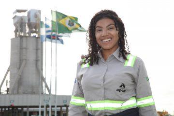 Na imagem, uma mulher negra com uma camisa social da Cimento Apodi sorri para a câmera. Ela tem cabelos cacheados pretos na altura do ombro, soltos. Atrás, há várias bandeiras tremulando, sendo uma delas do Ceará.