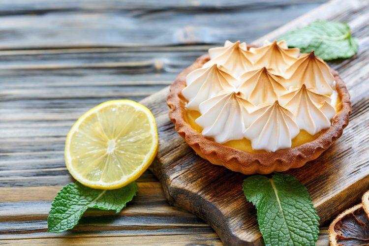 Cozinhar para vender: na imagem, há uma torta de limão em cima de uma tábua de madeira. Do lado esquerdo da imagem, há metade de um limão com folhas para ilustrar o sabor do doce.