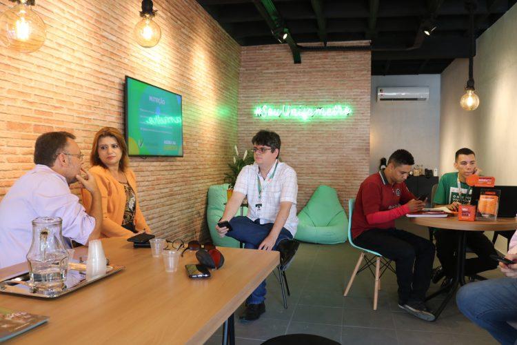 Consultoria: na imagem, a recepção do campus Aldeota, com mesa, cadeiras verdes e pessoas conversando ao redor de uma mesa de madeira.