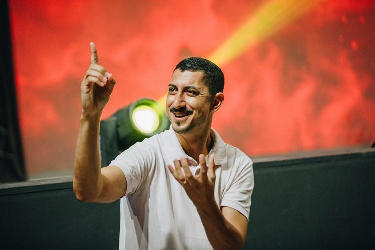 Na imagem, um homem jovem de camisa branca e cabelo e bigode pretos interpreta sinais. Atrás, há um holofote e luzes vermelhas, que indicam um show com acessibilidade.