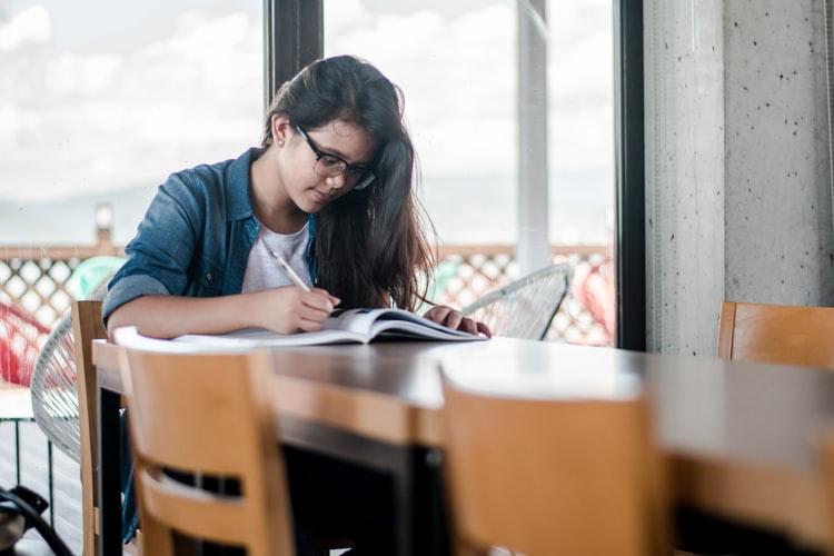 Concurso: na imagem, uma jovem estuda em uma mesa de madeira clara. Ela possui cabelo longo e escuro, que está solto, usa óculos e veste uma camisa branca com jaqueta jeans.
