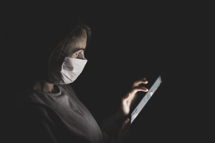 Covid-19: uma mulher de máscara mexe em um tablet no escuro. Ela está de perfil e usa a mão esquerda para manipular o equipamento.