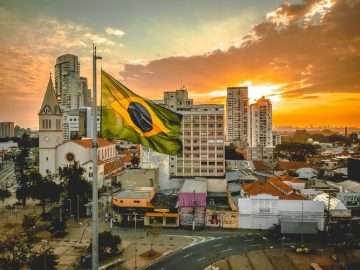 Curso sobre pós-pandemia no Brasil: na imagem, há uma paisagem urbana na luz do pôr-do-sol. Em primeiro plano, há uma bandeira do Brasil tremulando.