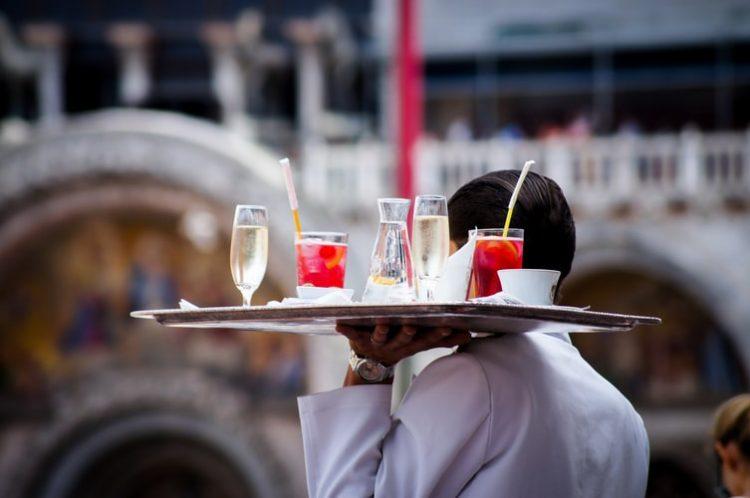 Cursos online da Unifor: entre as opções, há a modalidade de formação em garçom. Na imagem, um garçom de camisa branca está de costas, levando uma bandeja com drinks coloridos na mão esquerda.