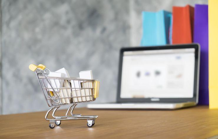 Miniatura de carrinho de comprar perto de notebook, em referência ao e-commerce