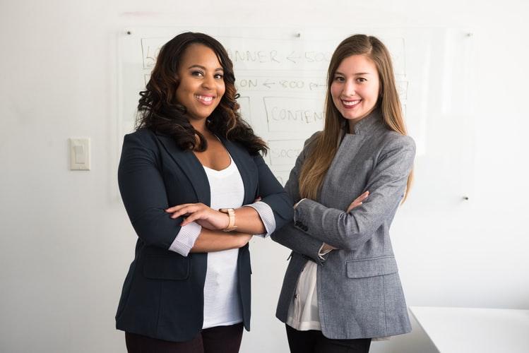 Empreendedorismo feminino: na imagem, há duas mulheres. A primeira, do lado esquerdo da foto, é negra e tem cabelos escuros; a segunda, do lado direito, é branca é tem cabelo loiro e longo. Ambas usam blazers e posam para a câmera com braços cruzados e sorrindo.
