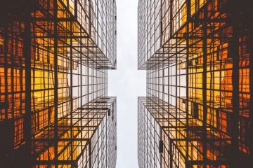 """Fotografia de Arquitetura. A imagem mostra, de baixo para cima, dois prédios paralelos e uma """"faixa"""" de céu"""" entre eles. A imagem é feita em tons de laranja e preto."""