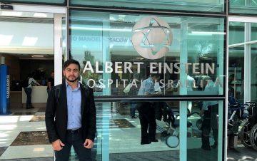 Na imagem, o CEO da Salvus, Maristone Gomes, posa em frente ao hospital Albert Einstein. Ele usa terno preto e camisa social azul com uma mochila preta.