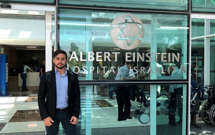 Internet das coisas é tema de artigo sobre saúde. Na imagem, o CEO da Salvus, Maristone Gomes, posa em frente ao hospital Albert Einstein. Ele usa terno preto e camisa social azul com uma mochila preta.