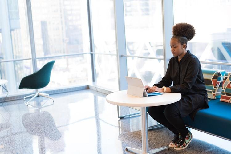 Liderança Negra Bayer: A imagem mostra uma sala ampla e claro, provavelmente em um ambiente corporativo. À direita da foto, há uma jovem negra que usa roupas pretas, tênis colorido e cabelo preso em um coque. Ela acessa um tablet branco em uma pequena mesa, também branca.