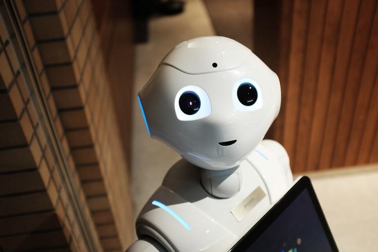 Robôs: na imagem, um robô branco olha para a câmera. Ele possui olhos e boca pretos e aparenta segurar um tablet preto.