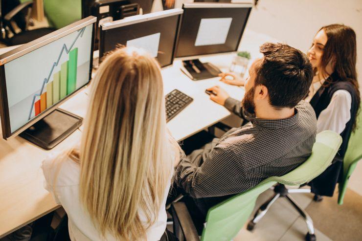 Mulheres e homem em frente a um notebook; vagas para TI e suporte estão abertas