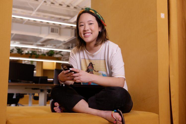 Trainee: na imagem, uma jovem garota com traços orientais está sentada em um sofá de cor clara. Ela sorri para a câmera e usa chinelos da Alpargatas.