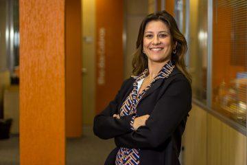Vendas digitais: na imagem, a diretora de Conteúdo da Avalara Brasil, Tricia Braga, sorri para a câmera com os braços cruzados. Ela usa uma camisa estampada nas cores laranja, branco e azul, um blazer preto e tem cabelos castanhos.