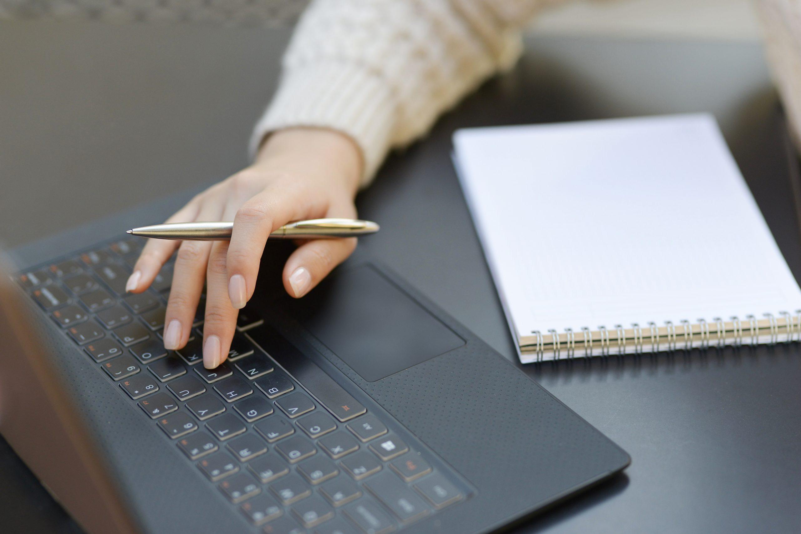 Mão de mulher com bloco de notas e digitando no notebook; Prefeitura de Groaíras está com inscrições abertas para concurso
