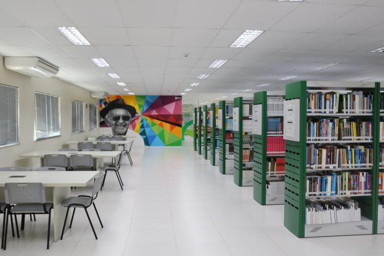 Cursos de curta duração: na imagem, a biblioteca da Unifametro, branca com estantes verdes e uma pintura colorida em uma das paredes.