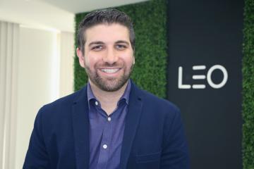 Redes sociais: Richard Vasconcelos, CEO da LEO Learning, sorri para a câmera. Ele é um homem branco que usa cabelo curto, barba e bigode, e está usando blazer e camisa azuis.