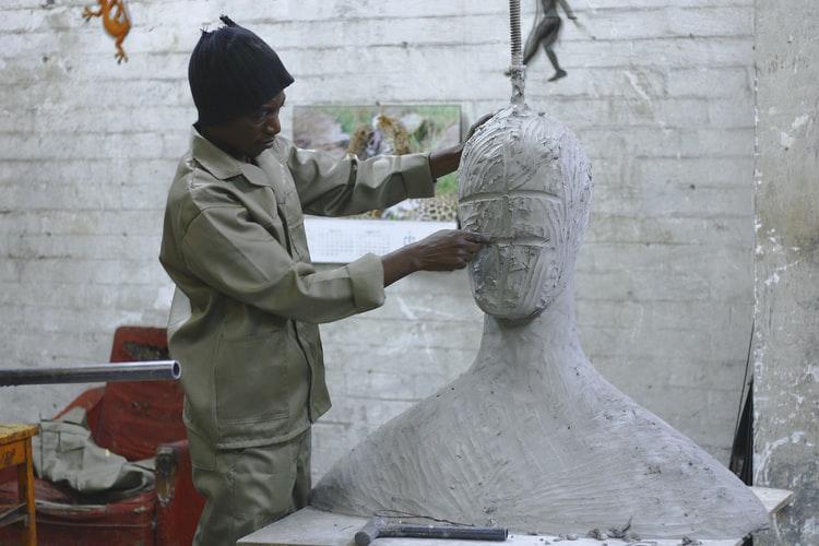 Capacitação para agentes culturais: na imagem, há um homem negro com um macacão bege e uma touca preta. Ele está esculpindo uma estátua que possui formato de busto, mas ainda não possui face.