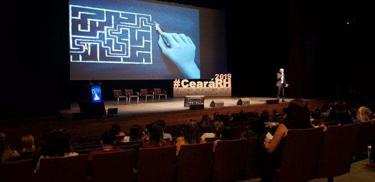 """CearáRH: Na imagem, uma palestra do evento de 2019. O público está em um auditório escuro e, no palco, há um telão e uma escultura com o nome """"#CearáRH"""" em branco."""