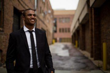 Lideranças negras: na imagem, um jovem negro sorri. Ele usa terno e gravata pretas e uma camisa social de cor branca e posa em frente à uma rua vazia.