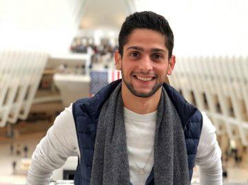 Na imagem, o arquiteto de soluções em nuvem Fernando Cardoso sorri para a câmera. Ele é branco, possui uma barba curta e usa uma camisa de manga comprida branca e um colete azul marinho, além de um cachecol de cor cinza.