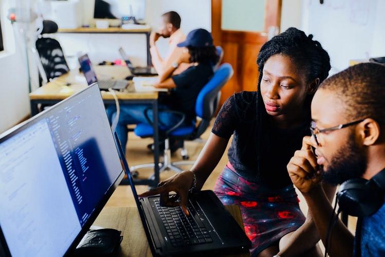 Programa de estágio: na imagem, dois jovens negros, um homem e uma mulher, estão sentados em frente a um computador. A jovem aponta para a tela. Eles estão em uma sala de aparência corporativa, com outras pessoas em computadores atrás.