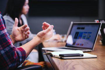 Recrutamento pode ser auxiliado por funcionários, diz especialista. Na imagem, duas pessoas conversam em frente a um noteebok aberto